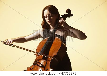 Young woman playing cello against colored background