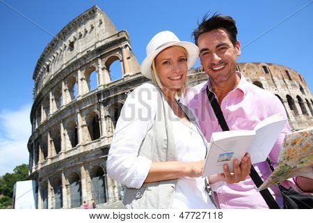 Casal lendo livro guia pelo Coliseu de Roma