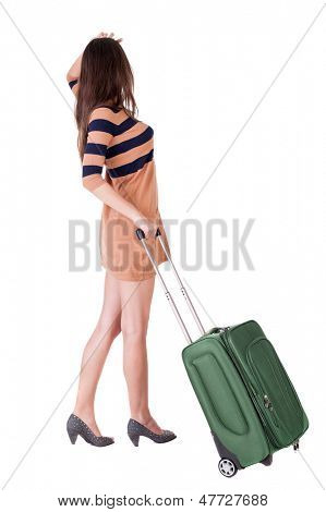 Back view brunette woman with suitcase looking up. Standing young girl. Rear view people collection. backside view person. Isolated over white background. languid girl in heels looks into the distance