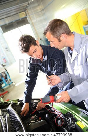 Trainer with student in repairshop checking on battery
