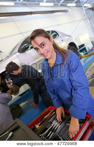 Smiling young woman in auto mechanics training class