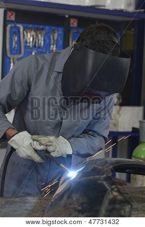 Closeup of solderer fixing bodywork