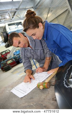 Instructor with student girl looking at bodywork instructions