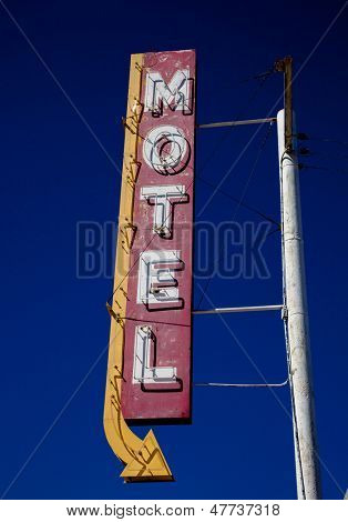 A vintage motel sign with an arrow in frount of blue sku