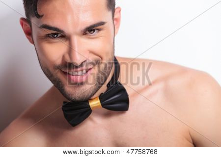 closeup of the face of a young topless man wearing a neckbow and smiling for the camera. on gray background