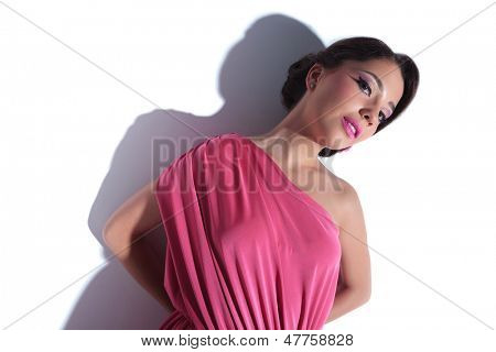 young beauty woman looking at the camera while holding her hands at her back. on a white background