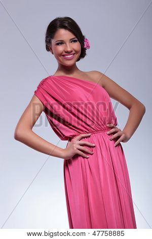 young beauty woman with lovely dress looks away while holding her hands on her hips. on a light gray background