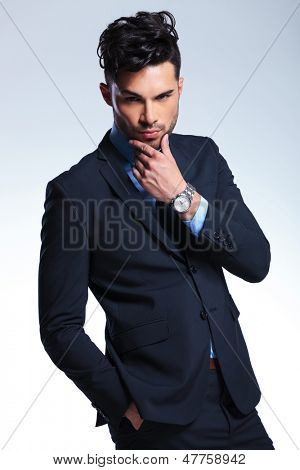 young business man looking at the camera with a thoughtful expression, holding a hand on his chin and the other in his pocket. on a gray background