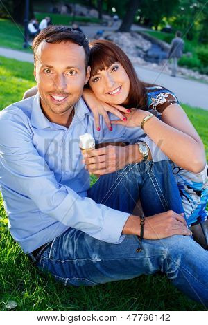 Happy smiling middle-aged couple  with ice-cream outdoors