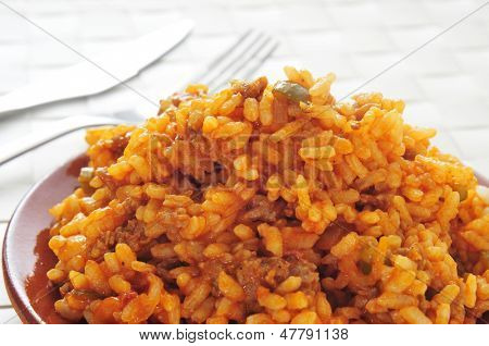 closeup of a earthenware plate with picadillo, a traditional dish in many latin american countries, mixed with rice