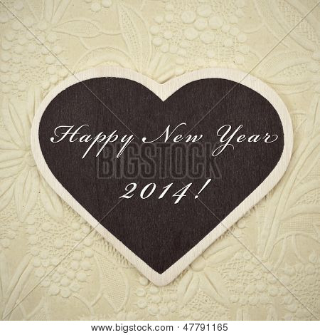 happy new year 2014 written in a heart-shaped blackboard on a vintage background, with a retro effect