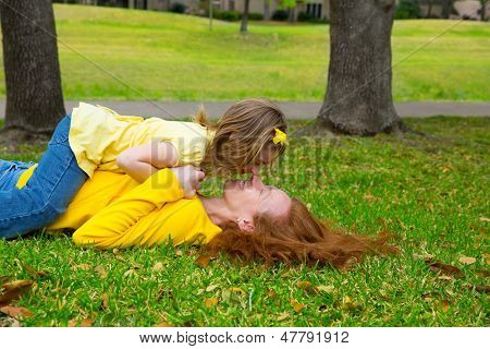 Mãe e filha nariz beijando deitado no gramado do parque ao ar livre