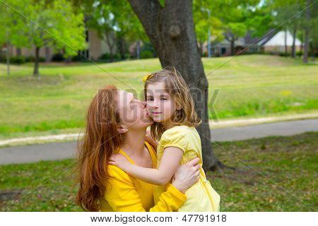 Mãe beijando a filha loira no verde parque ao ar livre, vestida de amarelo