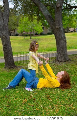 Daughter and mother playing lying on park lawn outdoor dressed in yellow