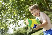 Young shirtless boy with water pistol in the park