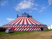 stock photo of circus tent  - Exterior of American circus marquee tent in stars and stripes of American flag blue sky background - JPG