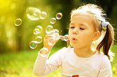 foto of blow-up  - Cute little girl is blowing a soap bubbles - JPG