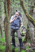 picture of boggy  - lost hiker in forest with mobile satelite navigation device   - JPG