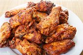 image of mesquite  - A white plate of spicy mesquite flavored chicken wings - JPG