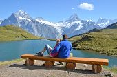stock photo of sea cow  - Travelers on a bench enjoying Alpine panorama - JPG