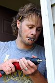 picture of hammer drill  - an attractive carpenter man is drilling a hole into a door frame on his home while holding screws in his mouth - JPG
