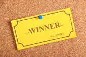 stock photo of raffle prize  - The winning golden raffle or lottery ticket pinned to a cork notice board as a concept for being a winner or achiever - JPG
