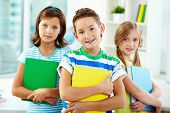 stock photo of diligent  - Portrait of three adorable kids holding textbooks - JPG