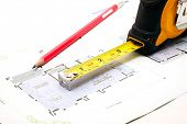 stock photo of numbers counting  - measuring tape and a pencil over a construction blueprint of a house - JPG