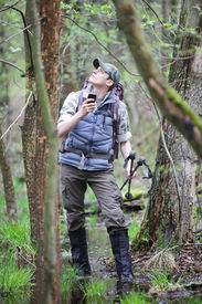 pic of boggy  - lost hiker in forest with mobile satelite navigation device   - JPG