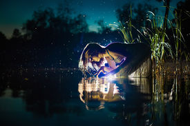 picture of paranormal  - Attractive witch is looking on the shiny water in the river - JPG