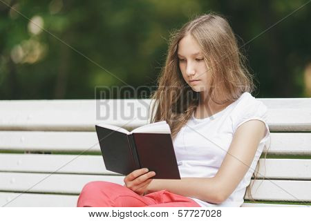 Young Teenage Girl Reading Book On Bench