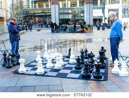 Two senior males ponder their moves as they play chess on the sidewalk of Westlake Park.