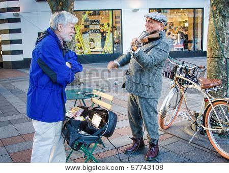 Senior male chats with street musician