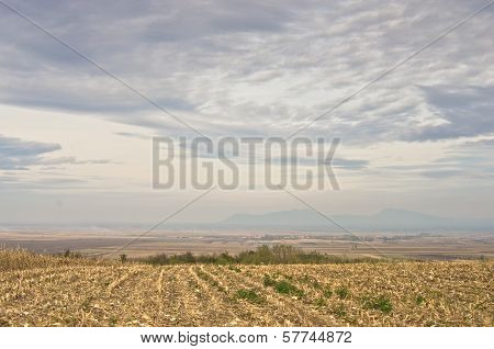 Flat prairie terrain under the rainy clouds with distant mountains in the background