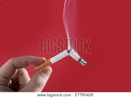 man hand holding broken cigarette smoking on red background