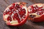stock photo of cut  - cut ripe pomegranate on an old wooden table closeup - JPG