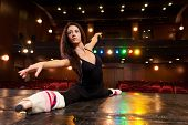 stock photo of leg-split  - Beautiful brunette dancer dressed in black training on the stage for her dance and doing side splits - JPG