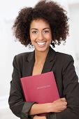 stock photo of vivacious  - Beautiful young African American woman with a curly afro hairstyle clutching a red file looking at the camera with a vivacious happy smile - JPG