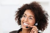 stock photo of receptionist  - Beautiful vivacious young African American client services call centre operator or receptionist smiling a warm friendly natural smile as she listens to a client speaking on her headset - JPG