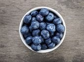 stock photo of ceramic bowl  - fresh blueberries in white bowl on wood table rustic style - JPG