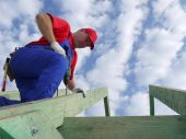 pic of purlin  - Carpenter drilling a hole in rafter framing beam - JPG