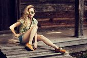 stock photo of leggings  - Trendy Hipster Girl Sitting on the Wooden Porch - JPG
