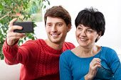 foto of selfie  - Son taking a selfie with his mother by using a smatphone - JPG