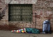 picture of sleeping bag  - Homeless Soul Sleeping on the Streets in a Sleeping Bag Outdoors - JPG