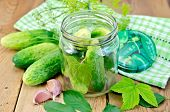Cucumbers In Jar With Leaves And Napkin On he Board