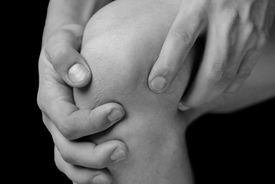 stock photo of stiff  - The man is touching the knee joint due to acute pain - JPG
