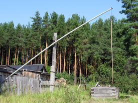 stock photo of shadoof  - shadoof in the countryside in the pine forests in Russia - JPG