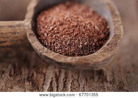 fine grated chocolate in old wooden spoon, shallow dof
