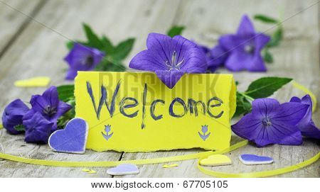 Welcome note card on wood table with purple flowers and hearts