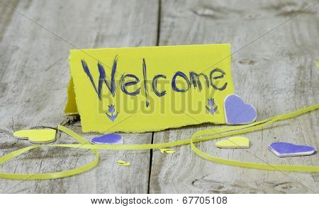 Welcome note card on rustic wood table with hearts and ribbon